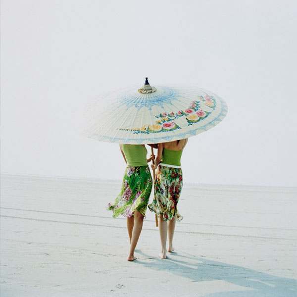 two women with pale skin under umbrella at beach 600 x 600